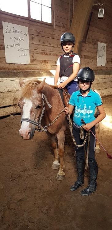 Enfants avec un cheval dans le manège de Château-d'Oex pendant un camp d'équitation à l'école d'équitation de Jean Blatti